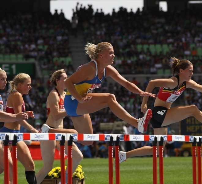 Ukraine's Natalia Dobrynska (C) and Belgium's Sara Aerts compete in the 100 metres hurdles of the women's heptathlon event at the International Association of Athletics Federations (IAAF) World Championships in Daegu on August 29, 2011.   AFP PHOTO / ADRIAN DENNIS