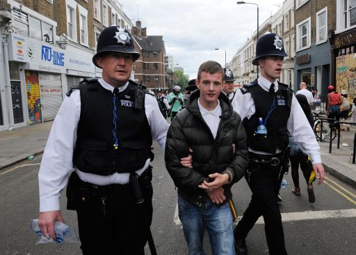 A man is detained by police during the  Notting Hill Carnival last day in London, on August 29, 2011. London's police were out in force as the Notting Hill Carnival got under way Sunday in a bid to stop Europe's biggest street festival descending into a repeat of this month's devastating riots. The two-day showcase of Caribbean culture in west London attracts up to a million revellers to watch troupes of dancers in exotic costumes perform on floats as powerful sound systems pump out music. AFP PHOTO/FACUNDO ARRIZABALAGA