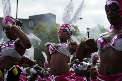 Women dance during the Notting Hill Carnival in London, on August 29, 2011. AFP PHOTO / CARL COURT