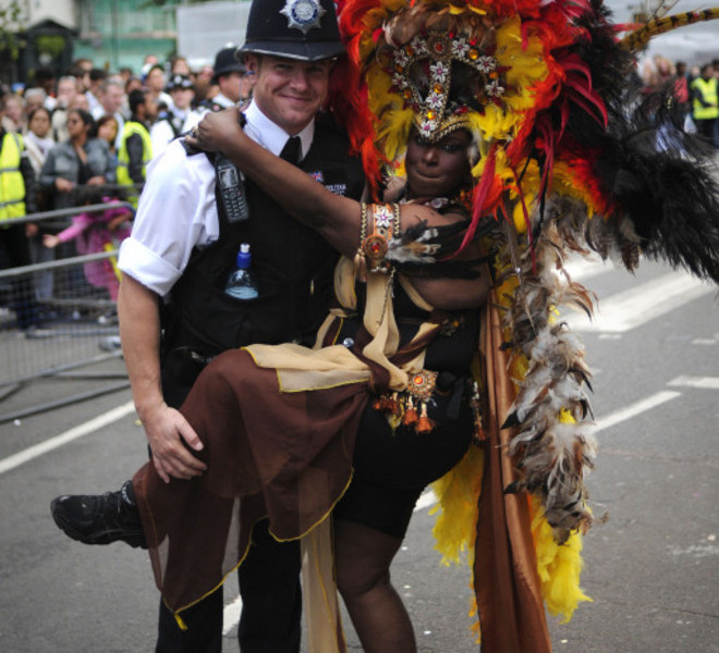 A performer dances with a police officer at the Notting Hill Carnival in London, on August 29, 2011.  Huge crowds of revellers gathered in London today for the finale of the Notting Hill Carnival, amid tight security to avoid a repeat of this month's riots at Europe's biggest street festival. AFP PHOTO / CARL COURT