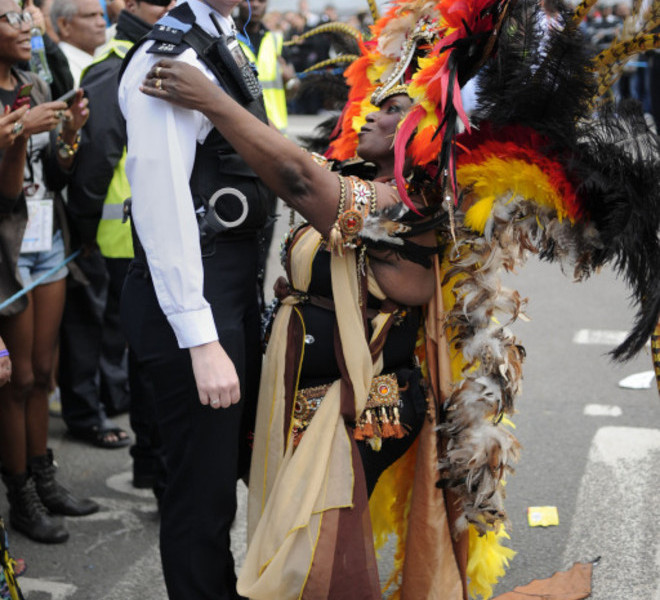 A performer dances with a police officer at the Notting Hill Carnival in London, on August 29, 2011. Monday, a public holiday, is the second and busiest day of the two-day festival which attracts around one million people, and there are fears gangs could hijack the event and go on the rampage in a repeat of the riots.AFP PHOTO / CARL COURT