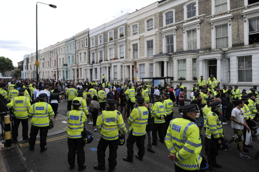 Police officers patrol a street during the Notting Hill Carnival in London, on August 29, 2011. AFP PHOTO / CARL COURT