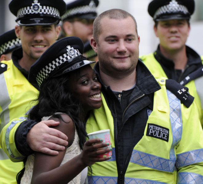 A woman laughs with a policeman after he placed his hat on her head during the Notting Hill Carnival in London, on August 29, 2011. AFP PHOTO / CARL COURT