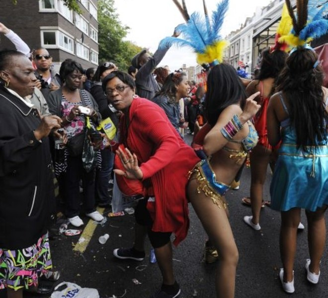 A performer dances with a member of the audience at the finale of the Notting Hill Carnival in London on August 29, 2011. Today is the second and busiest day of the two-day festival which attracts around a million people, and there were fears gangs could hijack the event and go on the rampage in a repeat of this month's riots. But the second day of festivities started peacefully with 6,500 police officers, the biggest number in recent years at the Caribbean-themed extravaganza, on duty as spectators watched Samba-style dancers perform on floats.   AFP PHOTO / FACUNDO ARRIZABALAGA