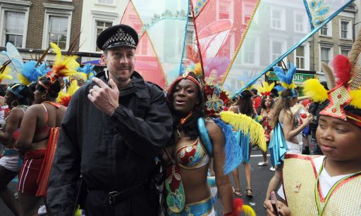 A performer poses with a British policeman at the finale of the Notting Hill Carnival in London on August 29, 2011. Today is the second and busiest day of the two-day festival which attracts around a million people, and there were fears gangs could hijack the event and go on the rampage in a repeat of this month's riots. But the second day of festivities started peacefully with 6,500 police officers, the biggest number in recent years at the Caribbean-themed extravaganza, on duty as spectators watched Samba-style dancers perform on floats.   AFP PHOTO / FACUNDO ARRIZABALAGA