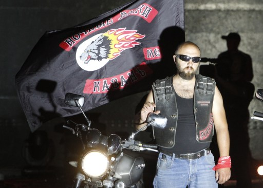 "A participant looks on during a visit of Russian Prime Minister Vladimir Putin to a bike festival in the southern Russian city of Novorossiisk on August 29, 2011. Putin described leather-clad bikers as brothers and boasted of the ""indivisible Russian nation"" after roaring into the biking rally on a Harley Davidson.   AFP PHOTO / POOL / Sergei Karpukhin"