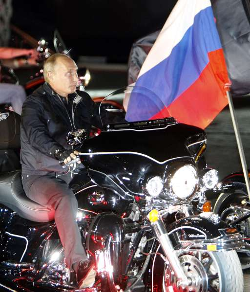 "Russian Prime Minister Vladimir Putin rides during a visit to a bike festival in the southern Russian city of Novorossiisk on August 29, 2011. Putin described leather-clad bikers as brothers and boasted of the ""indivisible Russian nation"" after roaring into the biking rally on a Harley Davidson.   AFP PHOTO / POOL / Sergei Karpukhin"