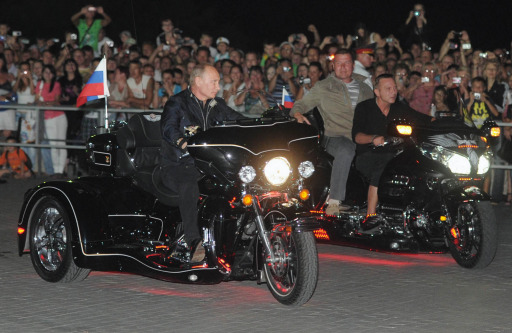 "Russian Prime Minister Vladimir Putin (L) rides a motorbike as he takes part in the 16th annual motorbike festival held by ""The Night Wolves"" youth organization in the southern Russian town of Novorossiysk, on August 29, 2011. AFP PHOTO / RIA NOVOSTI / POOL / ALEXEY DRUZHININ"