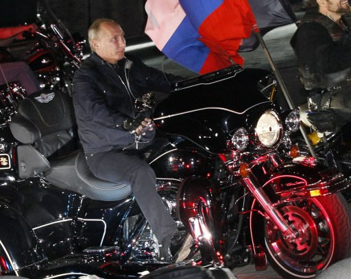 "Russian Prime Minister Vladimir Putin rides a motorcycle on August 29, 2011 at a bikers' festival in the Black Sea port of Novorossiysk, Russia. Putin described leather-clad bikers as brothers and boasted of the ""indivisible Russian nation"" after roaring into a biking rally on a Harley Davidson. AFP PHOTO / IVAN SEKRETAREV"