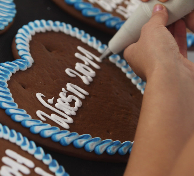 MUNICH, GERMANY - SEPTEMBER 08:  A confectioner letters a gingerbread heart with the slogan 'Wiesn 2011' (synonym for Oktoberfest) to be sold at the Munich Oktoberfest on September 8, 2011 in Aschheim near Munich, Germany. The world's largest beer festival takes place in Munich and will last this year from September 17 until October 3.  (Photo by Alexandra Beier/Getty Images)