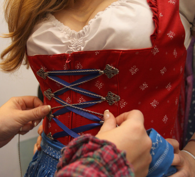 MUNICH, GERMANY - SEPTEMBER 08:  A customer is provided with embellishments as she tries on a traditional Bavarian Dirndl dress at a shop selling Dirndl dresses and leather trousers on September 8, 2011 in Munich, Germany. Dirndl dresses are famous to be worn during the world's biggest beer festival Oktoberfest which will last from September 7 to October 3, 2011 in Munich.  (Photo by Alexandra Beier/Getty Images)