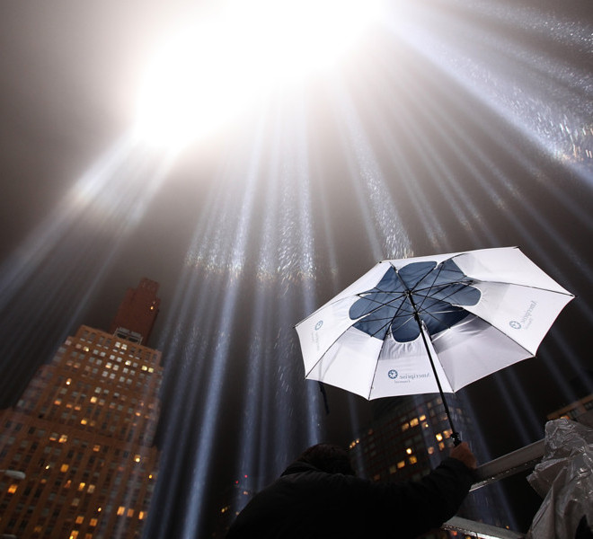 NEW YORK, NY - SEPTEMBER 07:  A worker holds an umbrella as he adjusts beams of the Tribute in Lights ahead of the tenth anniversary of the September 11 terrorist attacks on September 7, 2011 in New York City. The Tribute in Light is comprised of 88 7000 watt searchlights that beam into the sky near the site of the World Trade Center in remembrance of the September 11 attacks.  (Photo by Justin Sullivan/Getty Images)