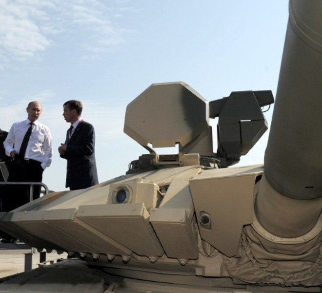 Russia's Prime Minister Vladimir Putin (L) listens to a guide as he stands atop a T-90AM tank during a visit to an arms exhibition in the Urals town of Nizhny Tagil, on September 9, 2011.  AFP PHOTO/ RIA-NOVOSTI POOL/ ALEXEY DRUZHININ