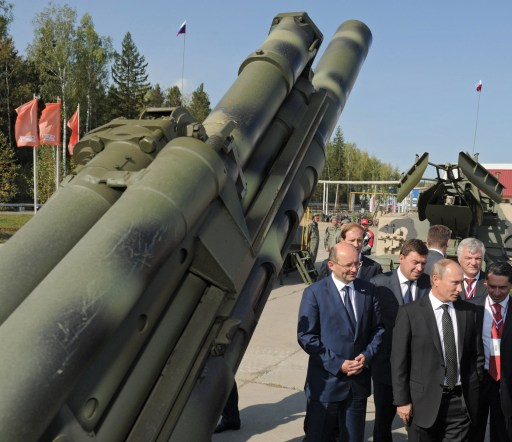 Russia's Prime Minister Vladimir Putin (R) listens to explanations during a visit at an arms exhibition in the Ural's town of Nizhny Tagil, on September 9, 2011. AFP PHOTO/ RIA-NOVOSTI POOL / ALEXEY DRUZHININ