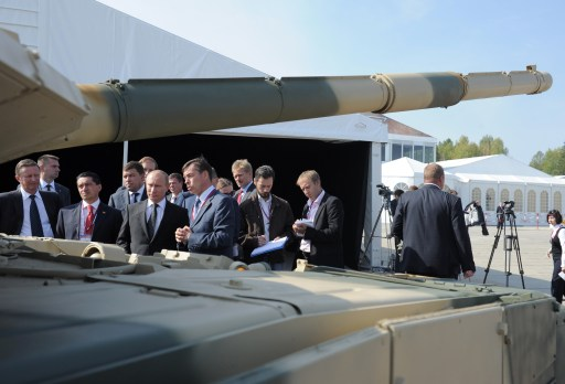Russia's Prime Minister Vladimir Putin (3rd L) listens to a guide as he stands  in front of  a T-90AM tank during a visit to an arms exhibition in the Urals town of Nizhny Tagil, on September 9, 2011.  AFP PHOTO/ RIA-NOVOSTI POOL/ ALEXEY DRUZHININ