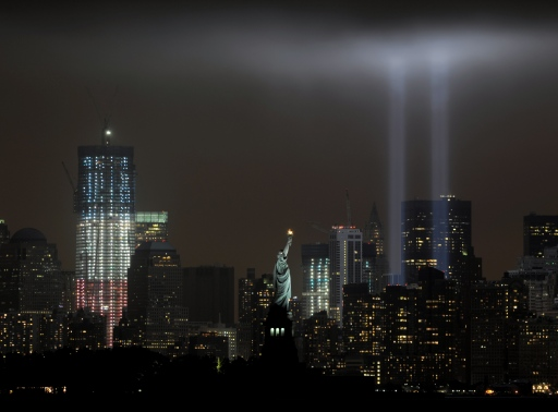 The annual ?Tribute in Light? memorial that echos the shape of New York's World Trade Center twin towers is illuminated with the  Statue of Liberty (C) and 1 World Trade Center (L) during the 10th Anniversary of the September 11, 2001 attacks at the lower Manhattan site of the World Trade Center September 11, 2011 in this view from Bayonne, New Jersey. AFP PHOTO/Stan HONDA