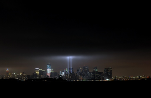 The annual ?Tribute in Light? memorial that echos the shape of New York's World Trade Center twin towers is illuminated during the 10th Anniversary of the September 11, 2001 attacks at the lower Manhattan site of the World Trade Center September 11, 2011 in this view from Bayonne, New Jersey. L-R in the New York skyline are the Empire State Building (with red,white and blue lights), 1 World Trade Center, the Statue of Liberty and the Brooklyn and Manhattan Bridges. AFP PHOTO/Stan HONDA