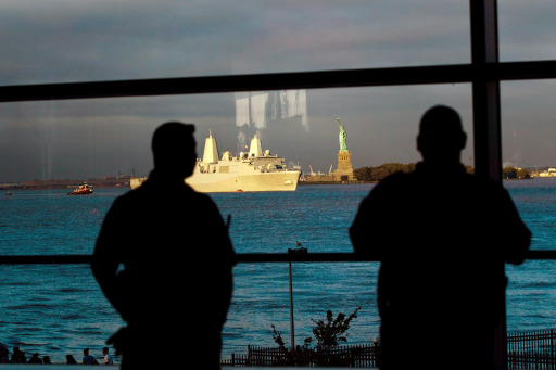 NEW YORK CITY- SEPTEMBER 11: Homeland security personnel look on as the USS New York sails past the Statue of Liberty in New York Harbor during the tenth anniversary of the September 11, 2001 terrorist attacks on September 11, 2011 in New York City. The USS New York is a ship forged from steele from the World trade centre and named in honor of the attacks on September 11, 2001. New York City and the nation are commemorating the tenth anniversary of the terrorist attacks which resulted in the deaths of nearly 3,000 people after two hijacked planes crashed into the World Trade Center, one into the Pentagon in Arlington, Virginia and one crash landed in Shanksville, Pennsylvania.   Daniel Berehulak/Getty Images/AFP== FOR NEWSPAPERS, INTERNET, TELCOS & TELEVISION USE ONLY ==