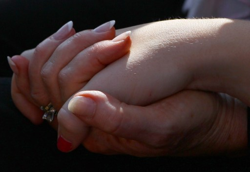 ARLINGTON, VA - SEPTEMBER 11: A mother and daughter hold hands during a remembrance ceremony at the Pentagon memorial September 11, 2011 in Arlington, Virginia. The nation is commemorating the tenth anniversary of the terrorist attacks which resulted in the deaths of nearly 3,000 people after two hijacked planes crashed into the World Trade Center, one into the Pentagon in Arlington, Virginia and one crash landed in Shanksville, Pennsylvania.   Win McNamee/Getty Images/AFP== FOR NEWSPAPERS, INTERNET, TELCOS & TELEVISION USE ONLY ==