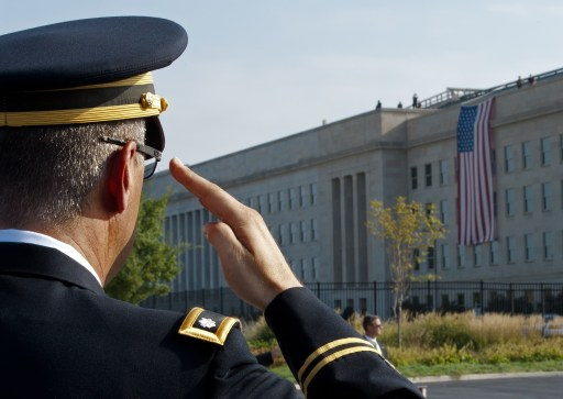 A US Military Officer salutes during the Pentagon 911 Observance ceremonies on the 10-year anniversary of the 911 terrorist attacks September 11, 2011 at the Pentagon in Washington, DC. The impact area where terrorists crashed the Boeing 757 is draped with the US flag that flew over the Pentagon days after the 911 attacks.          AFP Photo/Paul J. Richards