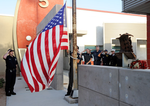 LAS VEGAS, NV - SEPTEMBER 11: Las Vegas Fire & Rescue members, including engineer Ken Dickenson (L) and Fire Chief Mike Myers (R) salute as an American flag that once flew over the Wrold Trade Center is hoisted to half-staff during a tolling of the bells service held to mark the time the South Tower of the World Trade Center fell during the September 11, 2001 terrorist attacks on September 11, 2011 in Las Vegas, Nevada. At right, a piece of steel from the World Trade Center is displayed. Las Vegas is joining the rest of the nation in commemorating the tenth anniversary of the attacks.   Ethan Miller/Getty Images/AFP== FOR NEWSPAPERS, INTERNET, TELCOS & TELEVISION USE ONLY ==