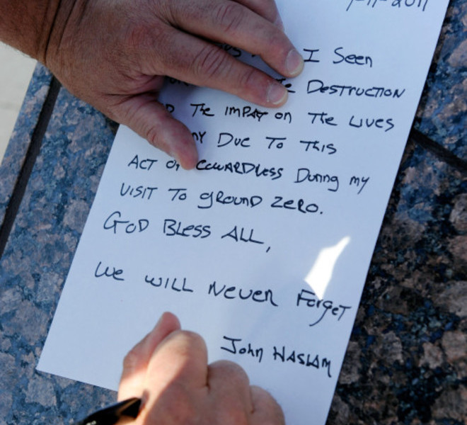 LAS VEGAS, NV - SEPTEMBER 11: Weymouth, MA Fire Department Deputy Chief John Haslan writes down his thoughts on the September 11, 2001 terrorist attacks at the Tribute to Heroes of 9/11 display outside the New York-New York Hotel & Casino September 11, 2011 in Las Vegas, Nevada. Las Vegas is joining the rest of the nation in commemorating the tenth anniversary of the terrorist attacks which resulted in the deaths of nearly 3,000 people after two hijacked planes crashed into the World Trade Center, one into the Pentagon in Arlington, Virginia and one crash landed in Shanksville, Pennsylvania.   Ethan Miller/Getty Images/AFP== FOR NEWSPAPERS, INTERNET, TELCOS & TELEVISION USE ONLY ==