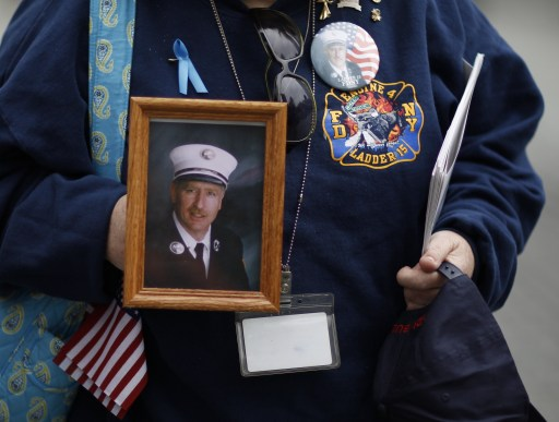 A New York City firefighter holds a photograph of a comrade during ceremonies marking the 10th anniversary of the 9/11 attacks on the World Trade Center, in New York, September 11, 2011. AFP PHOTO/POOL/Lucas Jackson