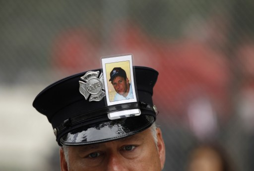 A New York firefighter with the image of a fellow firefighter Brian McAleese in his cap, attends ceremonies marking the 10th anniversary of the 9/11 attacks on the World Trade Center, in New York, September 11, 2011. AFP PHOTO/POOL/Lucas Jackson