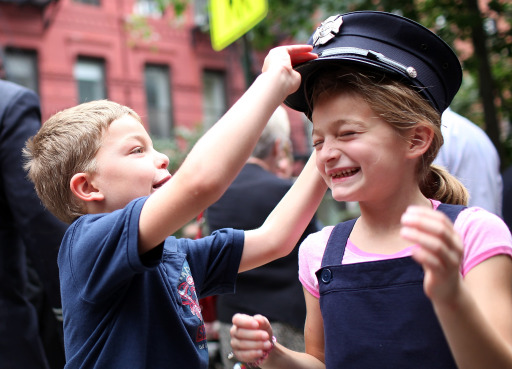 NEW YORK, NY - SEPTEMBER 11: Six year-old Peter Samuelson (L) and his sister, seven year-old Julia Samuelson, play with a firefighter hat after a memorial service at Old St. Pat's Church to mark the tenth anniversary of the September 11 terror attacks on the World Trade Center on September 11, 2011 in New York City. New York City firefighters are commemorating the 10th anniversary of the 9/11 terrorist attacks and honoring the 343 firefighters who died in the line of duty.   Justin Sullivan/Getty Images/AFP== FOR NEWSPAPERS, INTERNET, TELCOS & TELEVISION USE ONLY ==