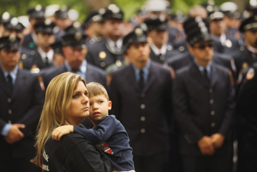 NEW YORK, NY - SEPTEMBER 11: Julia McCallister, wife of Martin County, Florida Fire Rescue firefighter Sean McCallister, holds son Sean at a memorial service for firefighters killed on 9/11 at the Firemen's Monument at Riverside Park on Septemnber 11, 2011 in New York City. Firegihters from around the world have converged on New York to take part in the anniversary services. New York City and the nation are commemorating the tenth anniversary of the terrorist attacks which resulted in the deaths of nearly 3,000 people after two hijacked planes crashed into the World Trade Center, one into the Pentagon in Arlington, Virginia and one crash landed in Shanksville, Pennsylvania.   Mario Tama/Getty Images/AFP== FOR NEWSPAPERS, INTERNET, TELCOS & TELEVISION USE ONLY ==