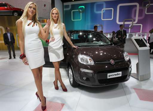 Fair hostesses pose next to a Fiat Panda car during the international motor show IAA (Internationale Automobil-Ausstellung) in Frankfurt/M, western Germany, on September 14, 2011. The world's biggest motor show, the IAA, is running from September 15 to 25, 2011.       AFP PHOTO / DANIEL ROLAND