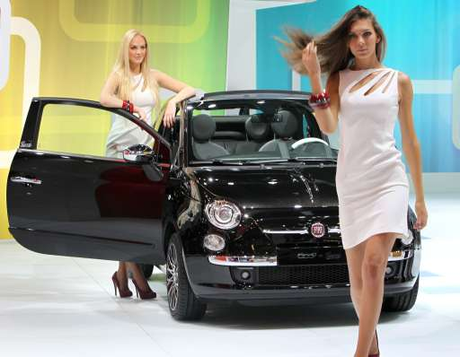 Fair hostesses pose next to a new Fiat 500 car during the international motor show IAA (Internationale Automobil-Ausstellung) in Frankfurt/M, western Germany, on September 14, 2011. The world's biggest motor show, the IAA, is running from September 15 to 25, 2011.       AFP PHOTO / DANIEL ROLAND