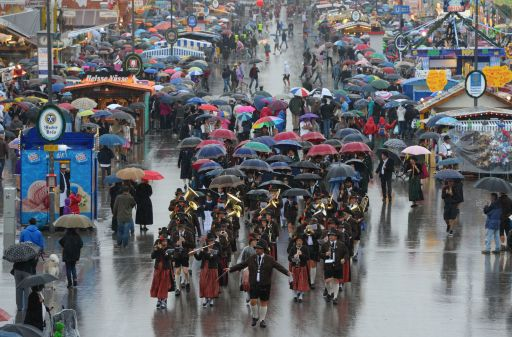 Musicians walk through the rain as they take part in the traditional costumes and riflemen parade of the Oktoberfest beer festival at the Theresienwiese fair grounds in Munich, southern Germany, on September 18, 2011. The world famous beer festival, which is excepted to attract around six million visitors, is running until October 3, 2011. AFP PHOTO/CHRISTOF STACHE