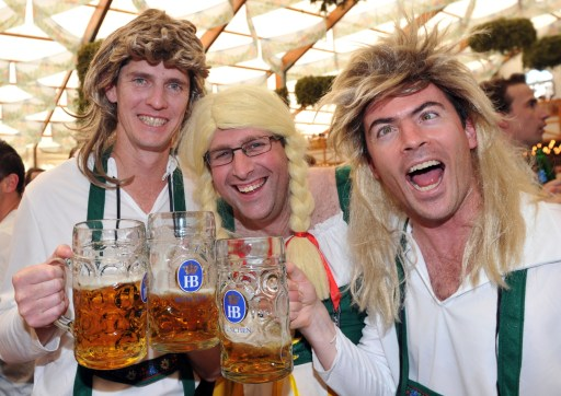 Men dressed with traditional Bavarian clothes wear blond wig as the share a toast in a tent at the start of the Oktoberfest beer festival at the Theresienwiese ground in Munich, southern Germany, on September 17, 2011. The 178th edition of the world's biggest beer festival which excepted to attract around six million visitors starts today and runs until October 3, 2011.  AFP PHOTO / FELIX HOERHAGER ++ GERMANY OUT