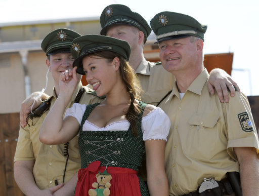 A young woman dressed with traditional Bavarian clothes wears a police hat as she poses with policemen at the start of the Oktoberfest beer festival at the Theresienwiese ground in Munich, southern Germany, on September 17, 2011. The 178th edition of the world's biggest beer festival which excepted to attract around six million visitors starts today and runs until October 3, 2011.  AFP PHOTO / ANDREAS GEBERT++ GERMANY OUT