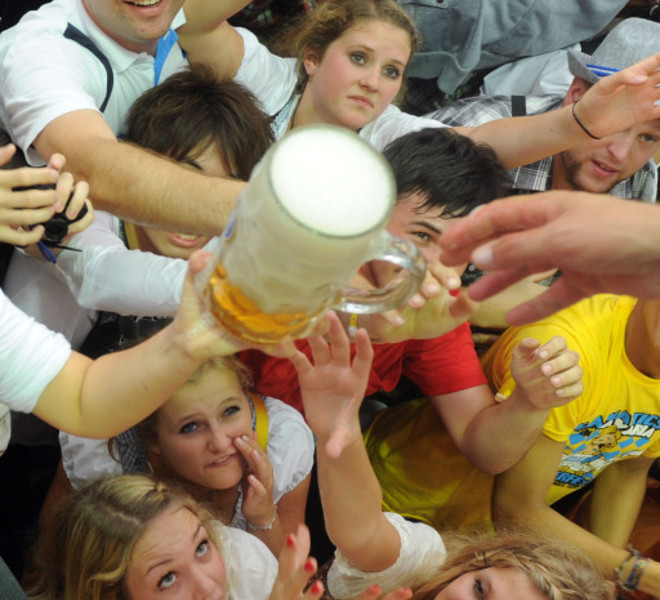 Visitors try to catch a beer mug in a festival tent at the start of the Oktoberfest beer festival at the Theresienwiese ground in Munich, southern Germany, on September 17, 2011. The 178th edition of the world's biggest beer festival which excepted to attract around six million visitors starts today and runs until October 3, 2011. AFP PHOTO / CHRISTOF STACHE