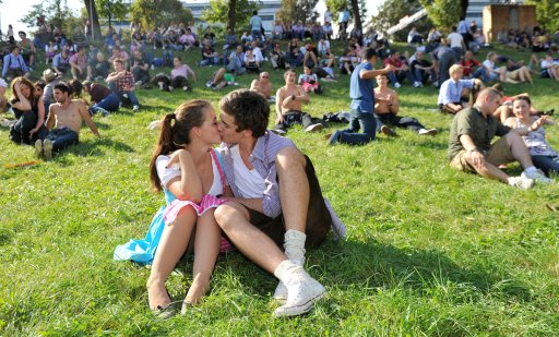 A couple kiss on a lawn at the start of the Oktoberfest beer festival at the Theresienwiese ground in Munich, southern Germany, on September 17, 2011. The 178th edition of the world's biggest beer festival which excepted to attract around six million visitors starts today and runs until October 3, 2011.  AFP PHOTO / Felix H?rhager ++ GERMANY OUT