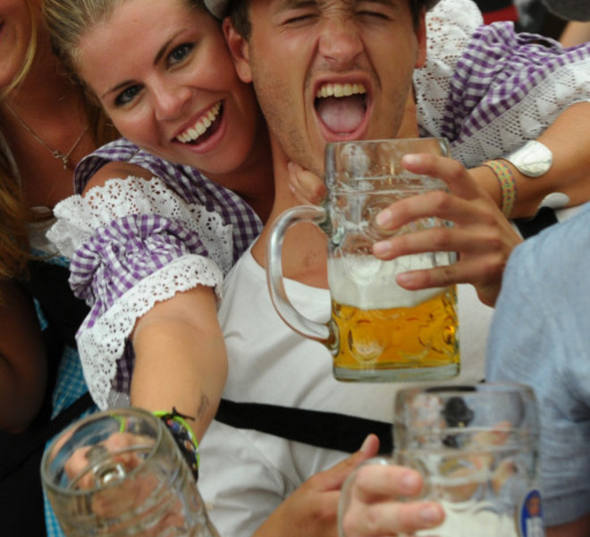 Visitors hold their beer mugs in a festival tent at the start of the Oktoberfest beer festival at the Theresienwiese ground in Munich, southern Germany, on September 17, 2011. The 178th edition of the world's biggest beer festival which excepted to attract around six million visitors starts today and runs until October 3, 2011. AFP PHOTO / CHRISTOF STACHE