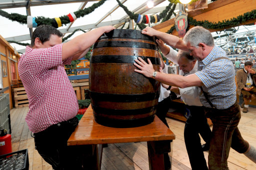 Three men prepare a beer barrel before the start of the Oktoberfest beer festival at the Theresienwiese ground in Munich, southern Germany, on September 17, 2011. The 178th edition of the world's biggest beer festival which excepted to attract around six million visitors starts today and runs until October 3, 2011.  AFP PHOTO / TOBIAS HASE++ GERMANY OUT