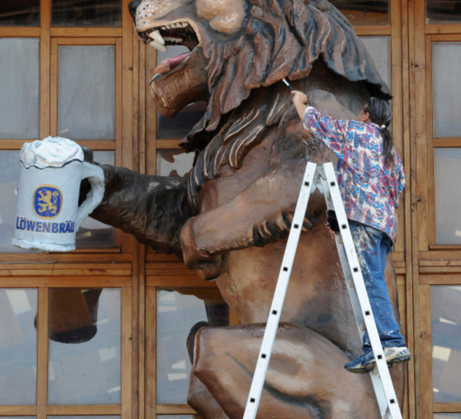 A man works on a lion sculpture, the logo of the Bavarian Loewenbraeu brewery, as preparations are under way for the Oktoberfest beer festival at the Theresienwiese fair ground in Munich, southern Germany, on September 14, 2011. This year's edition of the world's biggest beer festival Oktoberfest will open on September 17 and run until October 3, 2011.  AFP PHOTO / CHRISTOF STACHE