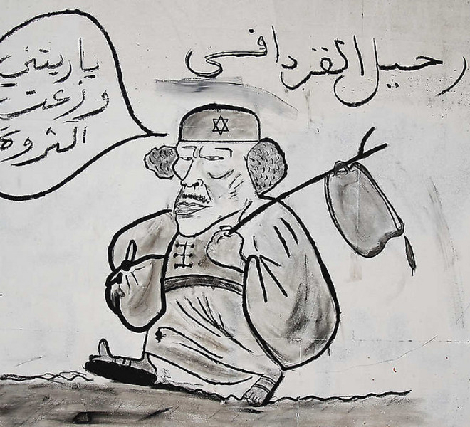 "A graffiti depicting Libya's ousted leader Moammar Gadhafi reading ""Gadhafi Going Away"" and saying in Arabic "" I should have distributed the wealth to the people"",  is seen on a street in Tripoli, Libya, Tuesday, Sept. 20, 2011. Libyan graffiti artists are taking advantage of their newfound freedom to make fun of ousted leader Moammar Gadhafi on the streets of Tripoli, after 42-years of authoritarian rule artists seem able to express themselves in public spaces. (AP Photo/Francois Mori)"