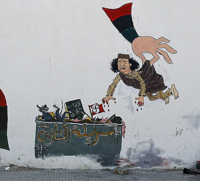 "A graffiti depicting ousted leader Moammar Gadhafi being thrown into a dustbin written in arabic ""Garbage of History"",  is painted on a wall in Tripoli, Libya, Sunday, Sept. 11, 2011. (AP Photo/Francois Mori)"
