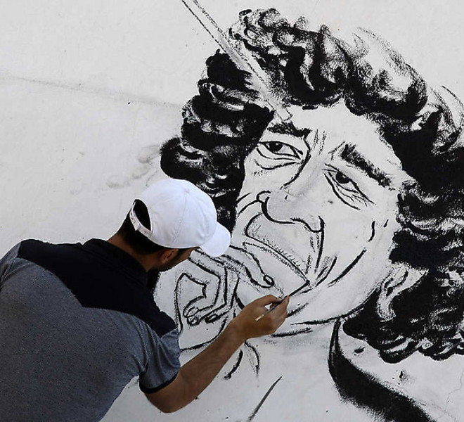 "A Libyan youth designs graffiti on a wall in Tripoli, Libya, Thursday, Sept. 8, 2011. The International Criminal Court is seeking Interpol's help in arresting ousted Libyan leader Moammar Gadhafi, the court's chief prosecutor said Thursday. Luis Moreno-Ocampo is asking the international police organization to issue a ""red notice"" for Gadhafi and says arresting him is a ""matter of time"". Gadhafi has not been seen in public for months. In an audio message broadcast Thursday by a pro-Gadhafi satellite TV channel based in Syria, he vowed never to leave Libya and called on supporters to keep fighting. (AP Photo/Francois Mori)"