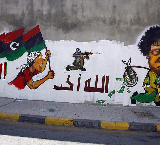 "Graffiti depicting ousted Libya leader Moammar Gadhafi, right, with ""Allah Akbar"" meaning ""God is Great"" written in Arabic is seen on a wall inTripoli, Libya, Monday, Sept. 12, 2011. NATO Secretary General Anders Fogh Rasmussen says the coalition will this week begin discussing whether to extend its operations in Libya. NATO has been bombing Moammar Gadhafi's forces since March under a United Nations mandate to protect Libyan civilians. But that mandate expires on Sept. 27. Rasmussen told reporters Monday that NATO is ready to continue operations as long as necessary, adding that an extension may be needed as remnants of Gadhafi's regime continue to pose a threat to civilians. (AP Photo/Francois Mori)"
