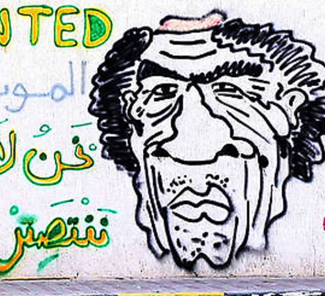 "A Libyan man stands in front a wall covered with pro-rebellion graffiti, including a cartoon of Libya's fallen leader Moamer Kadhafi, in the Tripoli suburb of Tajura on September 1, 2011, as rebel forces freshly installed in the Libyan capital braced for possible attacks from the remnants of Moamer Kadhafi's supporters on the 42nd anniversary of his rise to power. Arabic writing on the wall reads: ""Death to tyrants.. we don't surrender, we either win or die.. Long live Free Libya (L).""  MAHMUD TURKIA/AFP/Getty Images"