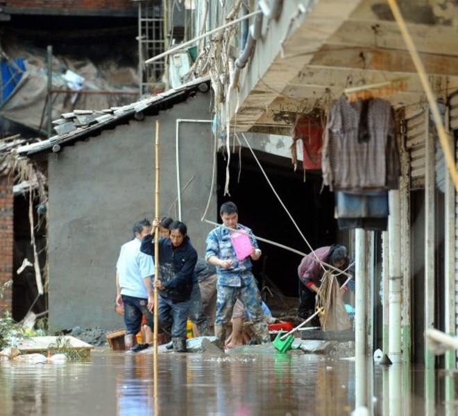 In this picture taken on September 19, 2011, local residents salvage their belongings after flood waters swamped the city of Guangan, southwest China's Sichuan province as unprecedented rains over the past week have swamped parts of northern, central and southwest China. Heavy rains and floods across China have left 57 people dead, dozens of others missing and hundreds injured, while more than a million residents have been evacuated from their homes, the government said.      CHINA OUT      AFP PHOTO