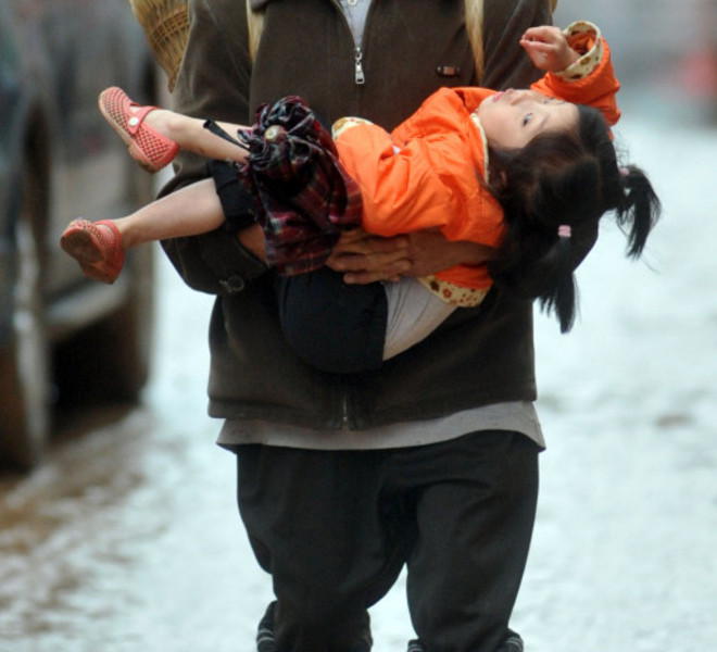 A Chinese man carries a young girl as he evacuates from the city of Guangan, southwest China's Sichuan province on September 19, 2011, as unprecedented rains over the past week have swamped parts of northern, central and southwest China. Heavy rains and floods across China have left 57 people dead, dozens of others missing and hundreds injured, while more than a million residents have been evacuated from their homes, the government said.      CHINA OUT      AFP PHOTO