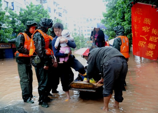 In this picture taken on September 19, 2011, a rescue team evacuates a family trapped in Guangan, southwest China's Sichuan province as unprecedented rains over the past week have swamped parts of northern, central and southwest China. Heavy rains and floods across China have left 57 people dead, dozens of others missing and hundreds injured, while more than a million residents have been evacuated from their homes, the government said.      CHINA OUT      AFP PHOTO