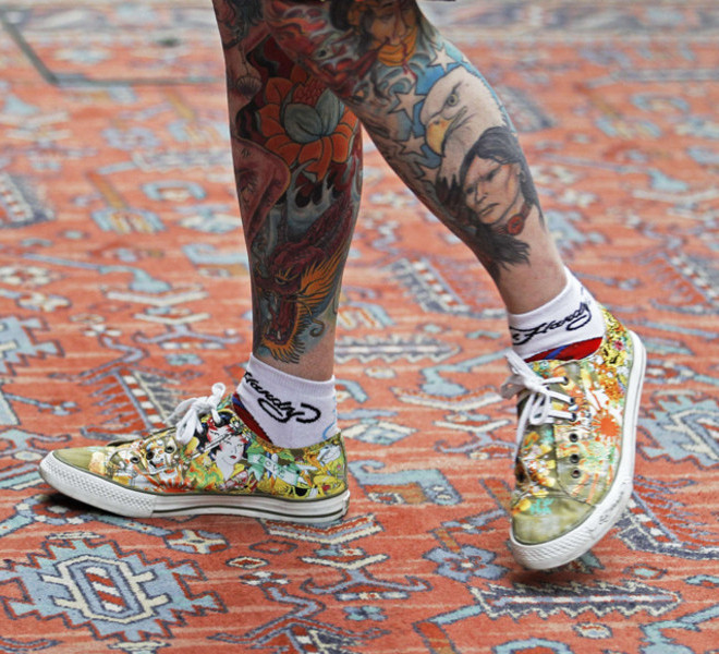 A man with tattooed legs walks across a coloured rug at the London International Tattoo Convention in London September 25, 2011.    REUTERS/Luke MacGregor  (BRITAIN - Tags: SOCIETY)