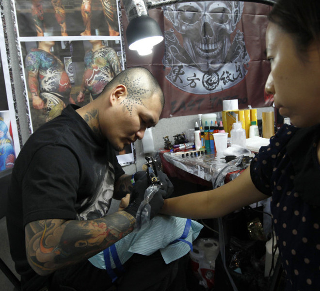 Tattoo artist Hua Wang of Taiwan tattoos his compatriot Yen Yen at the London International Tattoo Convention in London September 25, 2011. REUTERS/Luke MacGregor  (BRITAIN - Tags: SOCIETY ENTERTAINMENT)